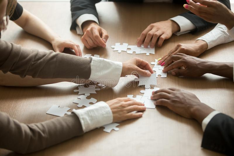 Diverse business people helping in assembling puzzle, teamwork s. Diverse business people helping in assembling puzzle, cooperation in decision making, team stock photo