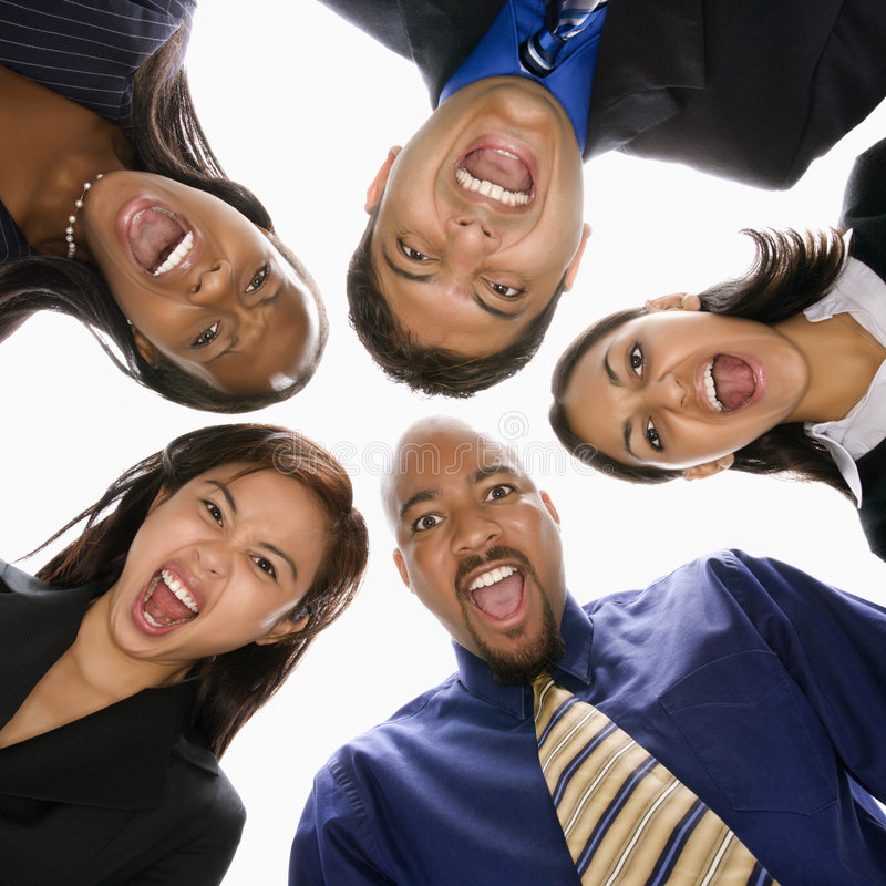 Diverse business people in huddle screaming. Low angle portrait of multi-ethnic business group of men and women in huddle screaming stock photography