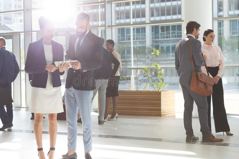 Diverse business people looking and discussing over digital tablet in lobby office. Front of view of diverse business people looking and discussing over digital royalty free stock photos