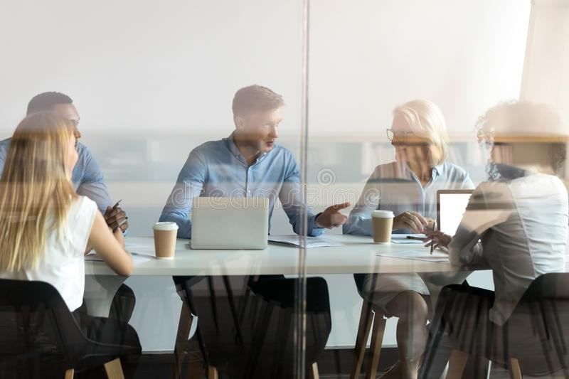 Diverse business people negotiating at table behind closed glass door royalty free stock image