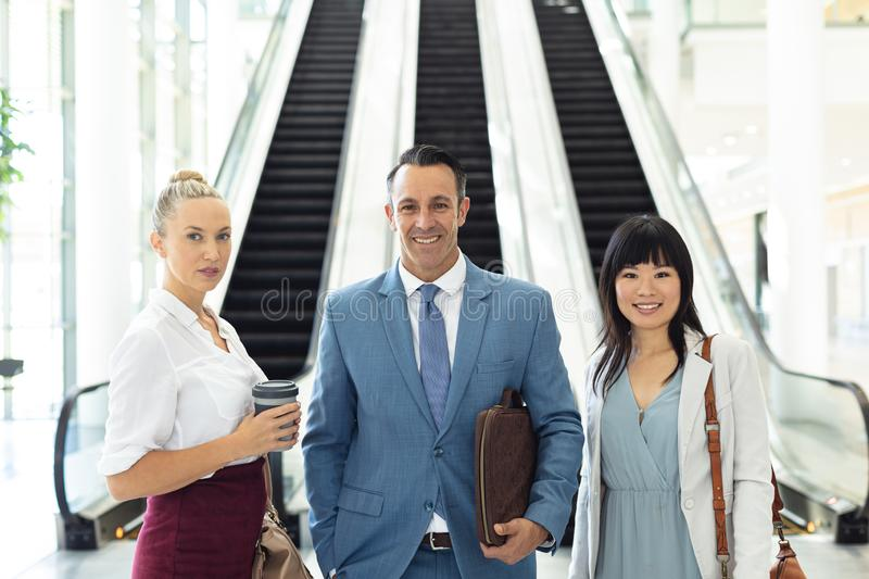 Diverse business people standing in front of escalators in modern office stock photo