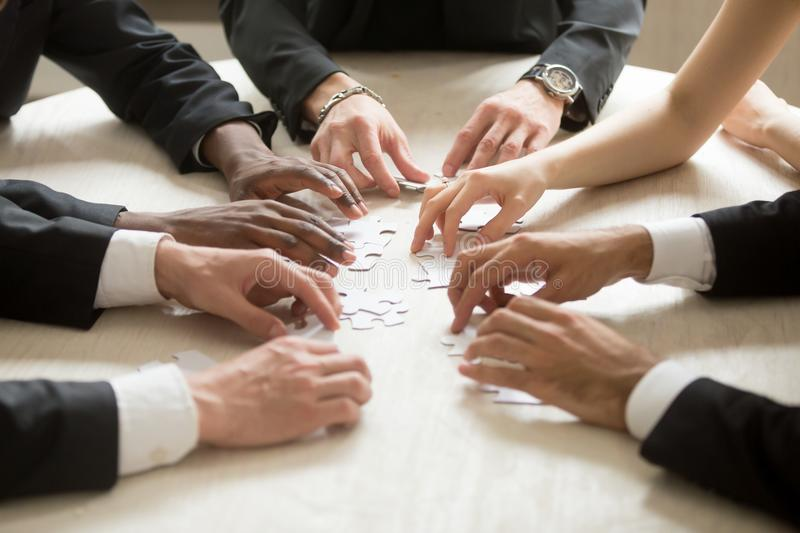 Business team assembling jigsaw puzzle, teamwork help support co. Diverse business team assembling jigsaw puzzle, hands joining pieces on desk in office, group stock photography