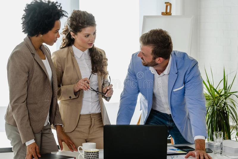 Diverse business team discussing work in their creative office stock photo
