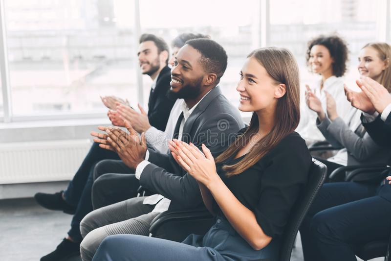 Diverse business team greeting speaker with applause royalty free stock image