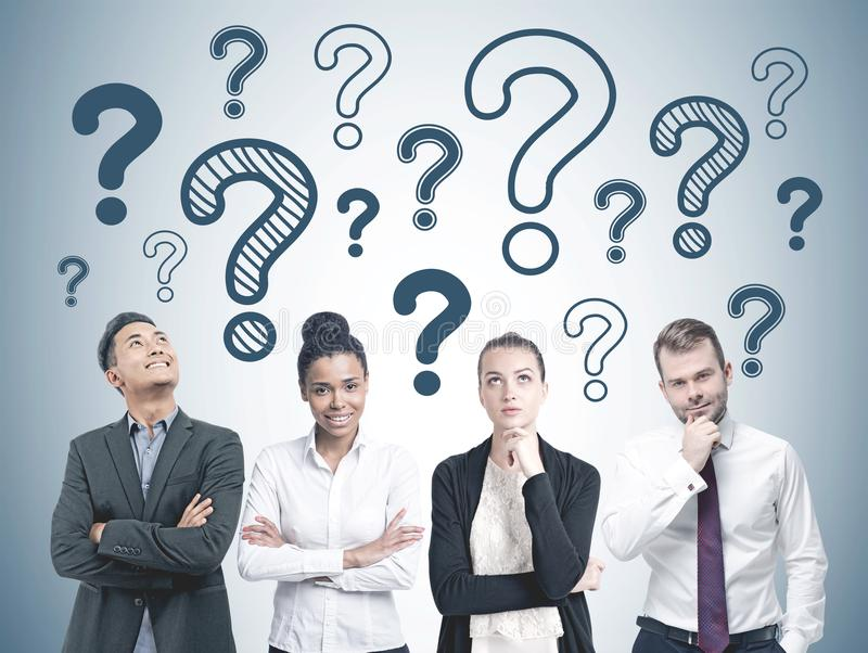 Diverse business team members, question marks royalty free stock image