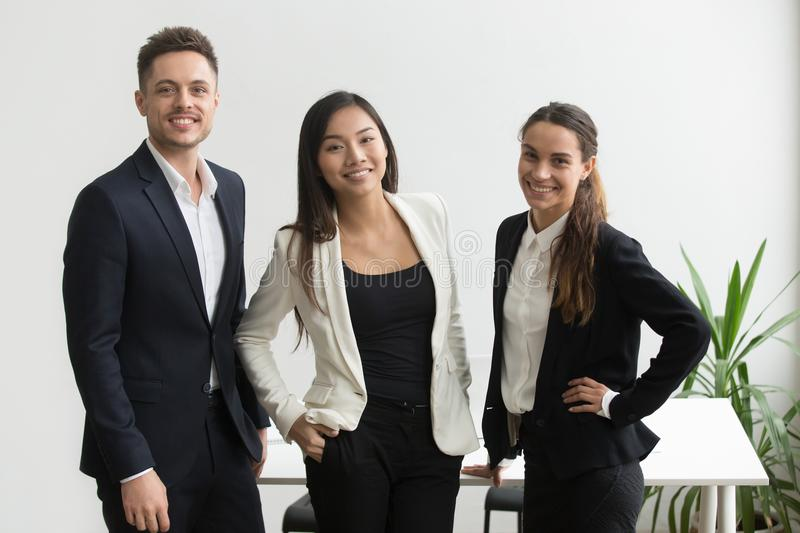 Millennial coworkers posing near office desk. Diverse business team of millennial coworkers posing near office desk smiling to camera. Company managers shooting royalty free stock photos