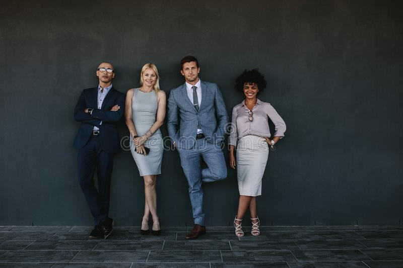 Diverse business team standing together against a wall stock photo