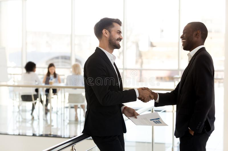 Diverse businessmen shaking hands introducing standing in modern. Diverse millennial businessmen shaking hands get acquainted introducing making first impression royalty free stock images