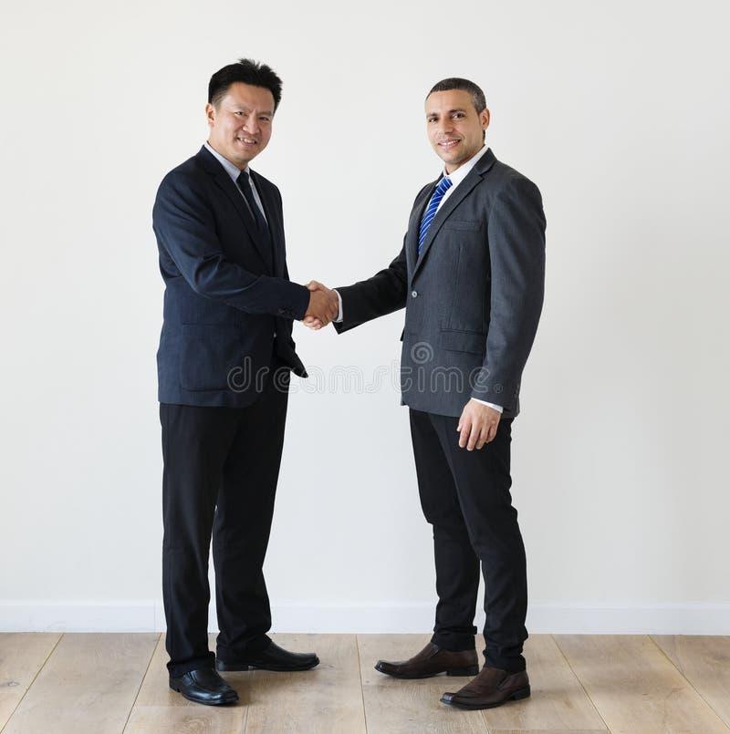 Diverse businessmen shaking hands together stock photography
