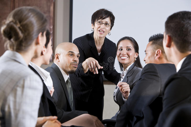 Diverse businesspeople conversing, woman at front stock photo