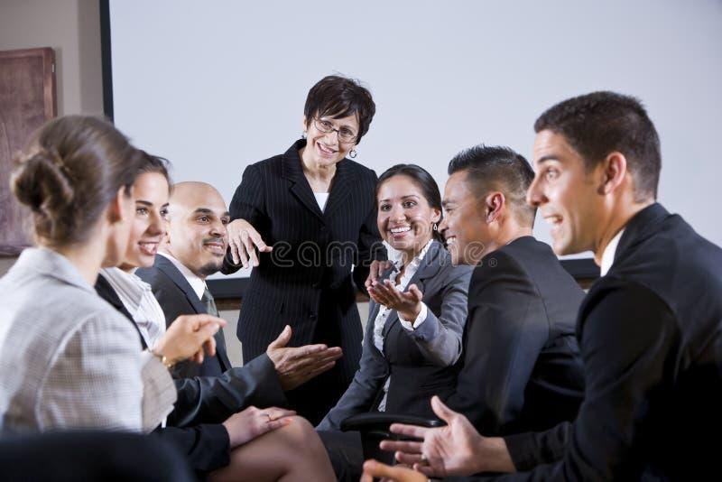 Diverse businesspeople die, vrouw bij voorzijde converseert royalty-vrije stock fotografie