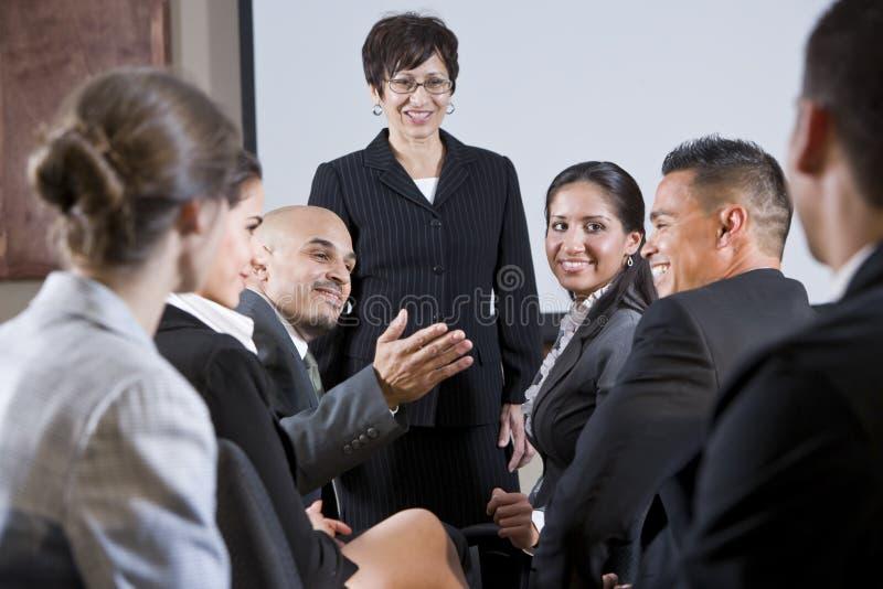 Diverse businesspeople die, vrouw bij voorzijde converseert stock fotografie