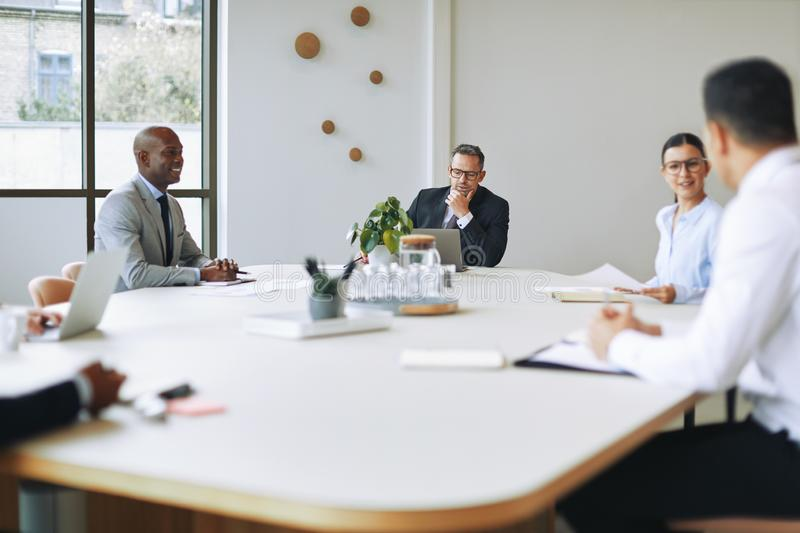 Diverse businesspeople having a meeting around a boardroom table stock images