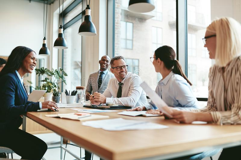 Diverse businesspeople laughing during a meeting around an offic royalty free stock photo