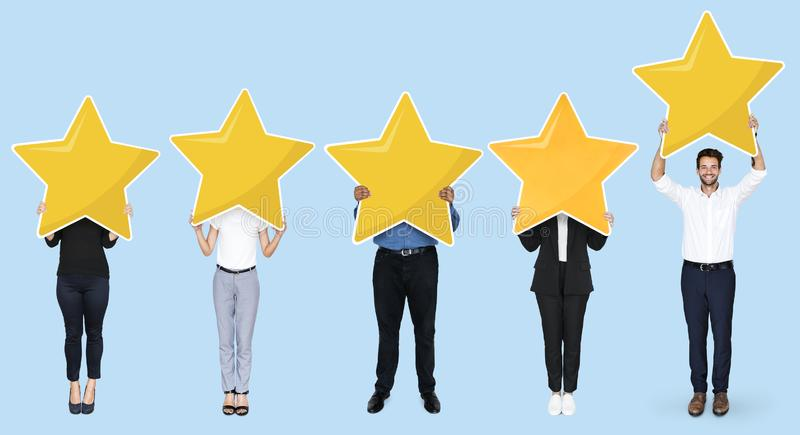 Diverse businesspeople showing golden star rating symbol stock image