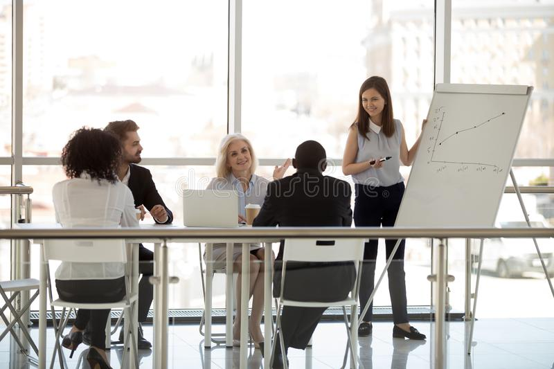 Diverse businesspeople sitting in boardroom discussing listening young coach royalty free stock images