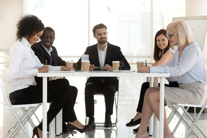 Diverse businesspeople sitting at desk, parties signing contract royalty free stock photography