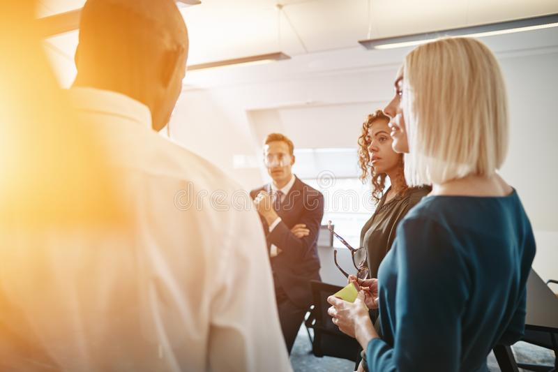 Diverse businesspeople talking together in a bright modern offic stock photos