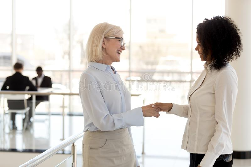 Diverse businesswomen shaking hands greeting each other. Middle aged company owner greeting new employee hired worker. Mixed race young female has first working royalty free stock photos
