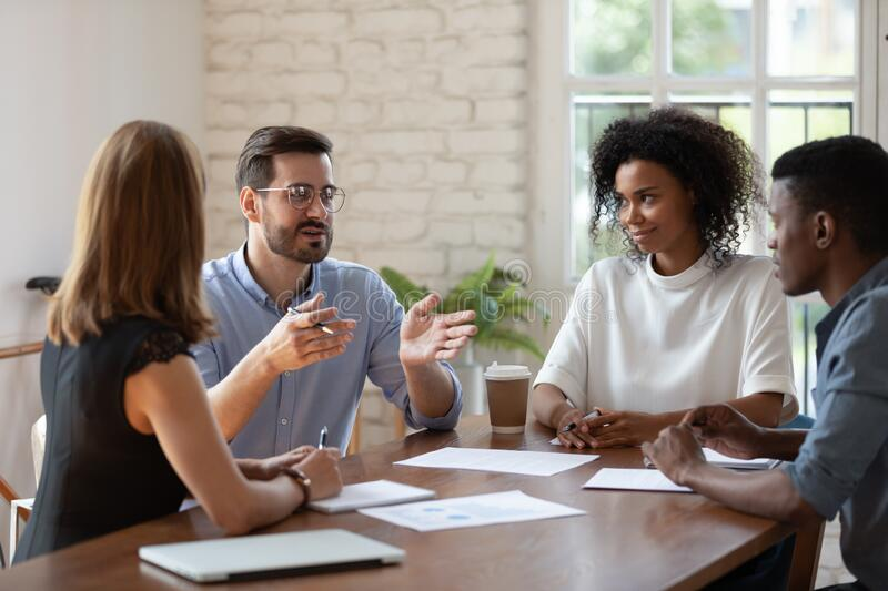 Diverse colleagues brainstorming, discussing project at meeting in boardroom royalty free stock photos