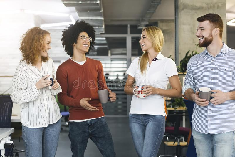 Diverse colleagues enjoying communication in modern office. Coffee break. Diverse colleagues enjoying communication in modern office, free space royalty free stock photos