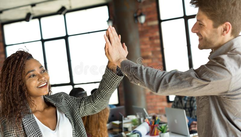 Diverse colleagues giving high five at office meeting royalty free stock images