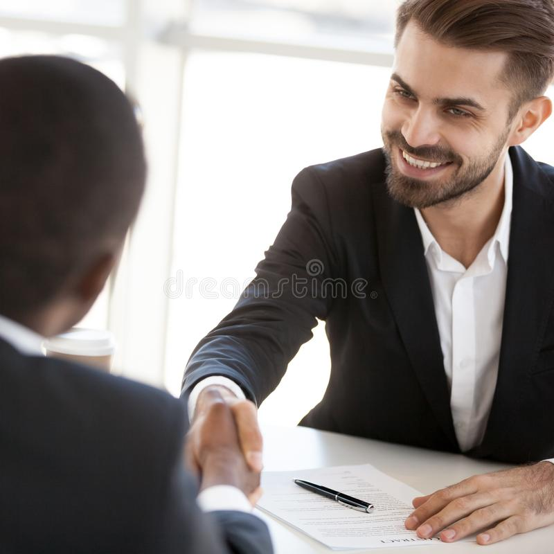 Diverse colleagues handshake closing business deal at briefing. Excited Caucasian businessman shake hand of black colleague closing deal at business briefing royalty free stock image