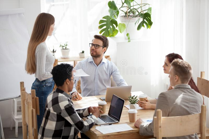 Female employee stand reporting at office meeting. Diverse colleagues talk cooperating at casual business meeting in office, millennial female employee stand royalty free stock photo
