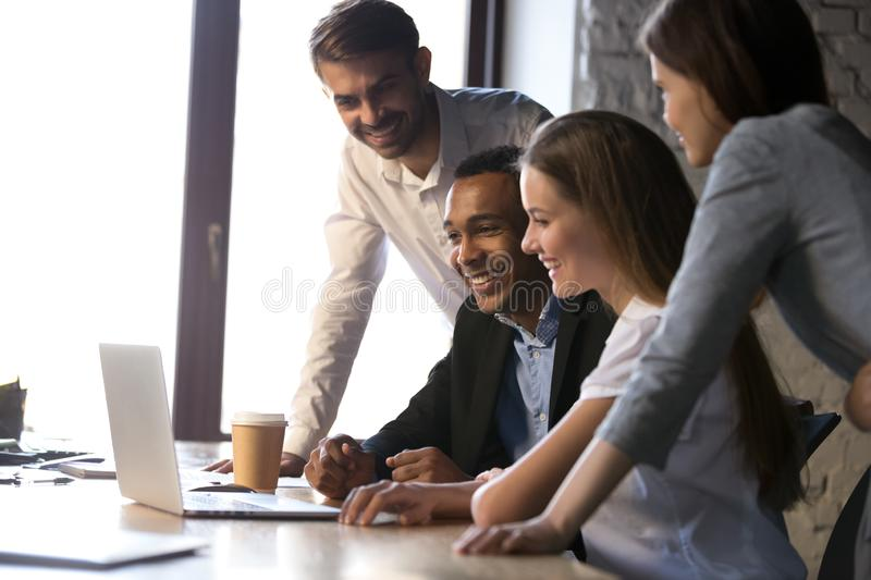 Diverse colleagues using laptop together, having fun during break royalty free stock photo