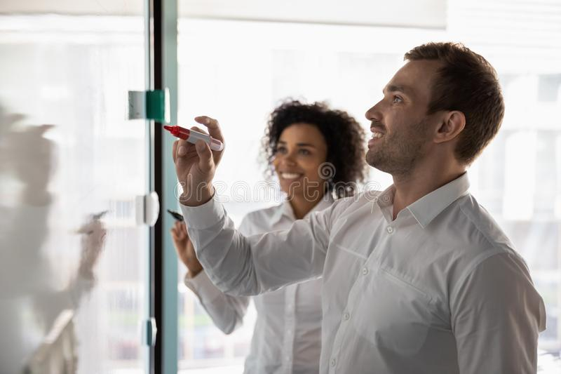 Diverse colleagues writing on flip chart, working on business strategy stock photo
