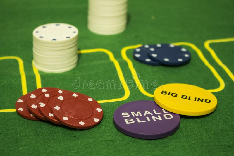 Diverse colorful chips for carding games and gamble with two medals writed `Small Blind` and `Big Blind` useful for Texas Hold`em. Kind of poker over a green royalty free stock photo