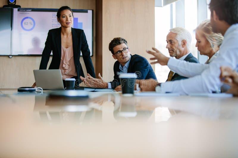 Diverse commerciële groep die een vergadering in bestuurskamer hebben stock fotografie