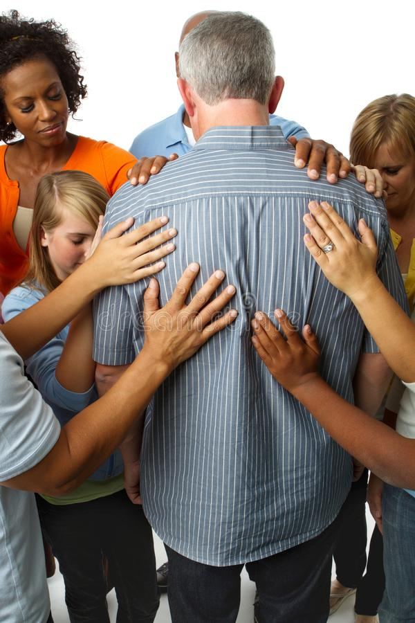 Community of people praying for an older man. royalty free stock photos