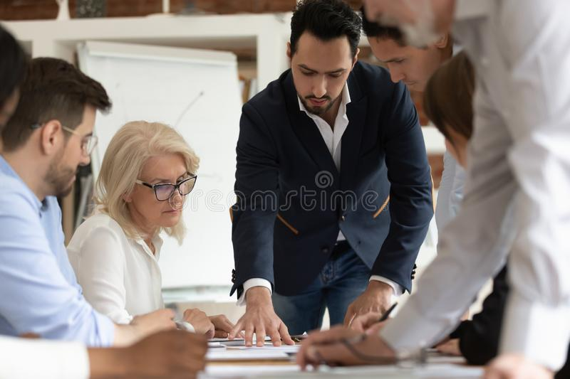 Diverse employees brainstorm discussing project at briefing. Diverse company employees brainstorm cooperating at company briefing in office, multiracial royalty free stock photos