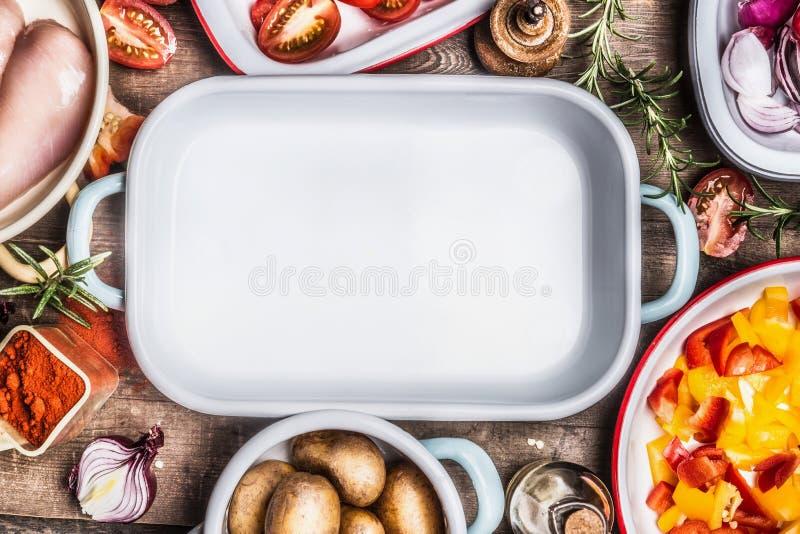 Diverse dieet kokende ingrediënten: kippenborst, besnoeiingsgroenten in kommen, kruiden en kruiden rond lege geëmailleerde braadp royalty-vrije stock afbeelding