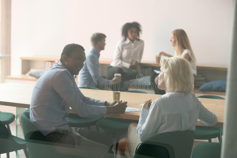 Diverse employee talk discussing ideas at break in boardroom. Diverse employees talk discussing business ideas or sharing thoughts cooperating at coffee break stock images