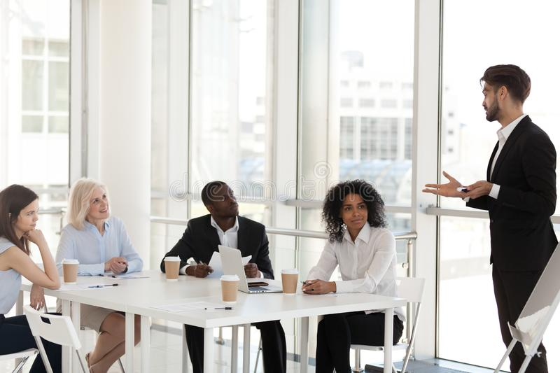 Diverse employees at company meeting with business coach or mentor royalty free stock image