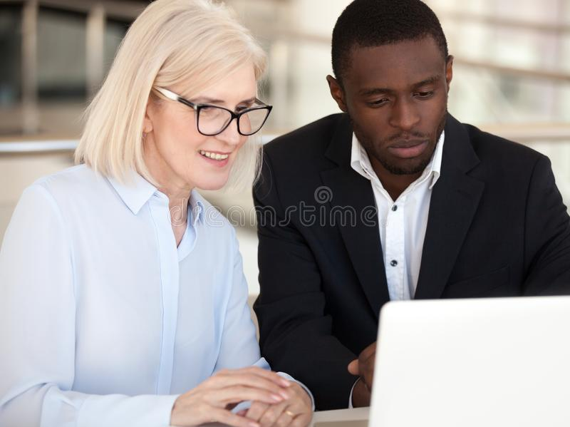 Diverse employees coworking using computer at office meeting royalty free stock images