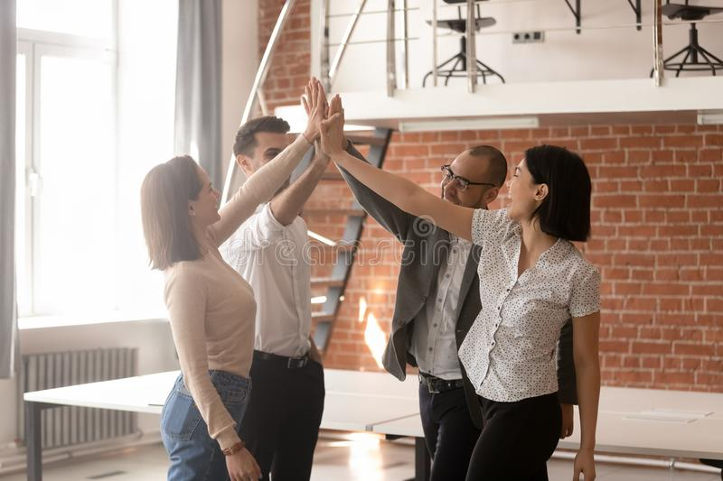 Diverse employees giving high five, celebrating successful work results royalty free stock images
