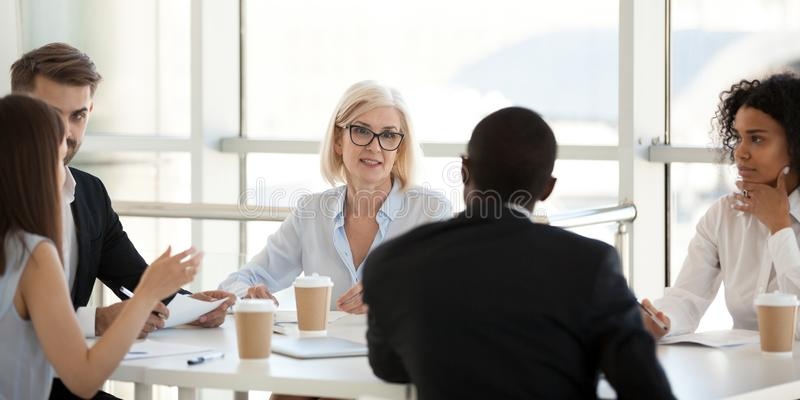 Diverse employees negotiate during business meeting in office stock image