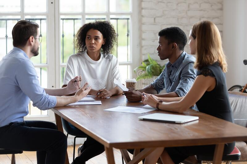 Diverse employees team discussing project strategy at corporate briefing stock images