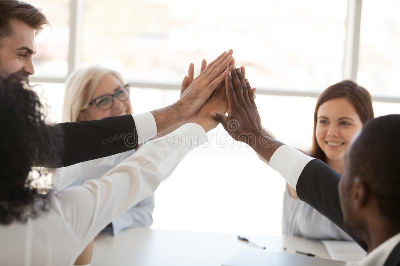 Diverse employees team giving high five at meeting close up royalty free stock images