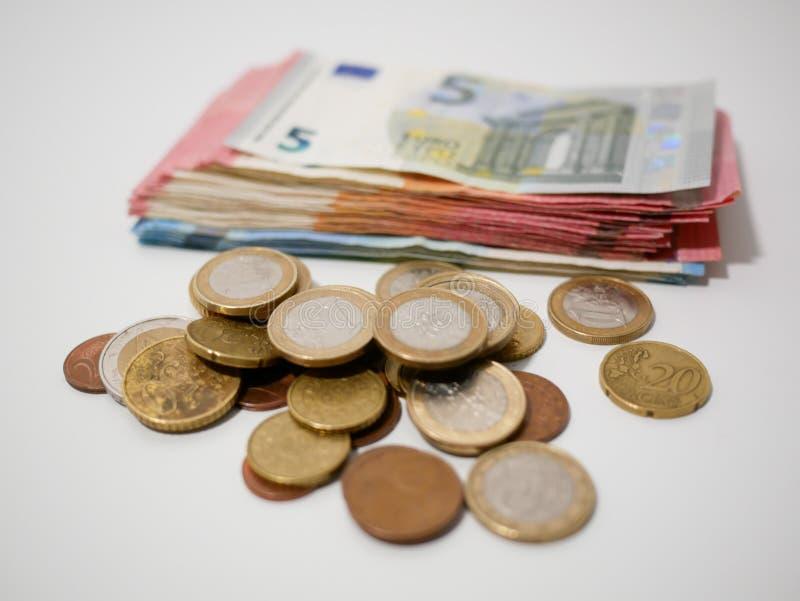 Diverse Euro muntstukken en bankbiljetten op een wit bureau Nota's en muntstukken van diverse benamingen stock foto's