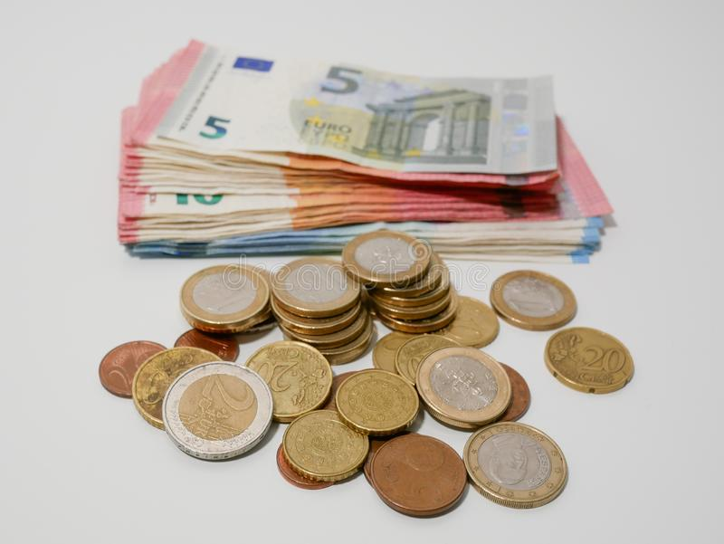 Diverse Euro muntstukken en bankbiljetten op een wit bureau Nota's en muntstukken van diverse benamingen stock afbeelding