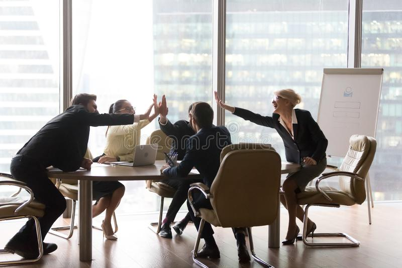 Diverse executive business team give high five in modern office. Diverse executive business team give high five in office, international corporate staff group royalty free stock images