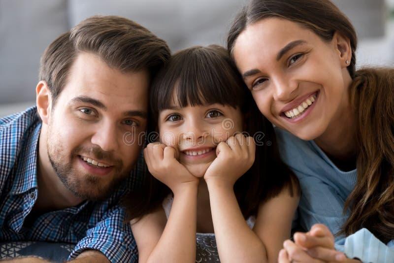 Diverse familie die op warme vloer liggen die camera bekijken royalty-vrije stock foto