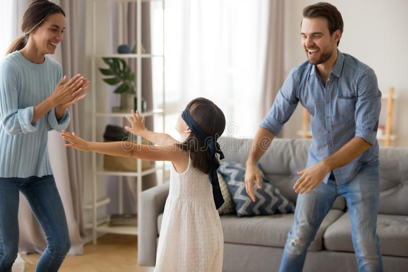 Diverse family playing hide and seek at home. Blindfolded girl catching mother and father playing hide and seek in living room at home, cheerful parents having royalty free stock image