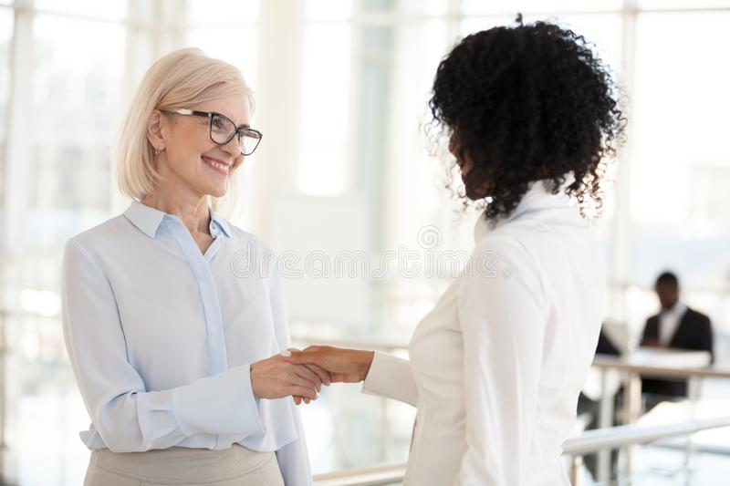 Smiling diverse female colleagues handshake meeting in hallway. Diverse female colleagues handshake meeting in office hallway, having casual conversation royalty free stock photos