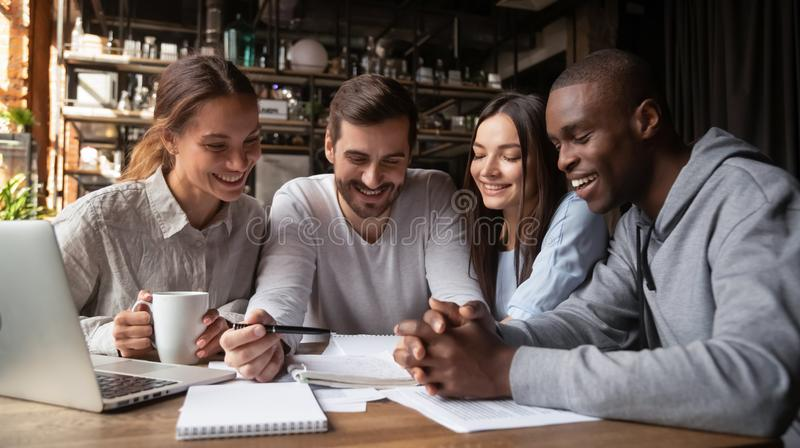 Diverse friends analyzing documents together, doing homework in cafe royalty free stock photos