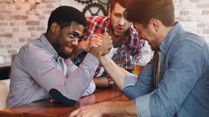 Diverse Friends Arm Wrestling And Drinking Beer At Bar. Or Pub royalty free stock photo